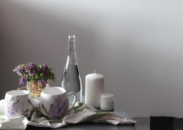 Flores moradas, dos tazas, velas, tazón con agua en la mesa