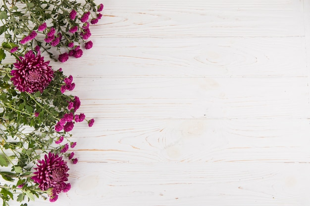 Flores moradas esparcidas sobre mesa de madera.