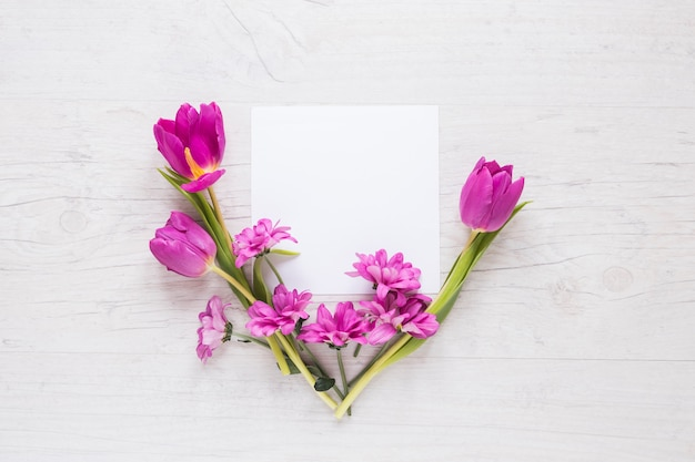 Flores moradas con papel en blanco sobre mesa.
