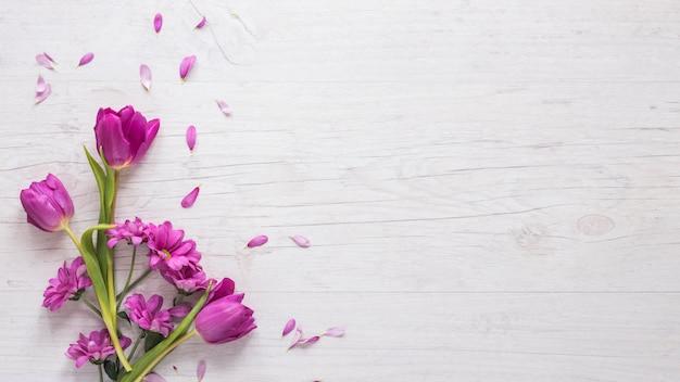 Flores moradas con pétalos en mesa.