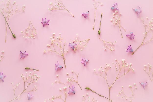 Flores moradas con ramas de plantas en mesa.