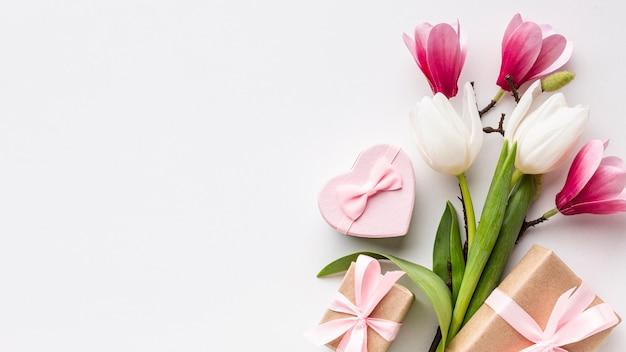 Flores y objetos femeninos sobre fondo blanco con espacio de copia