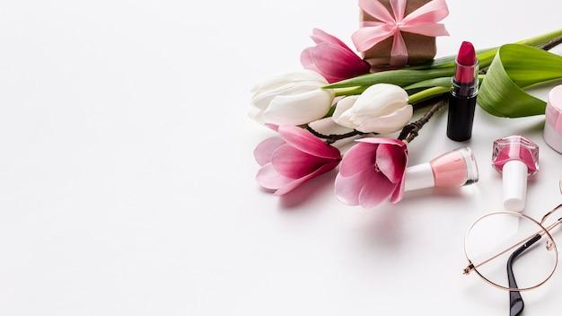 Flores y objetos femeninos sobre fondo blanco.