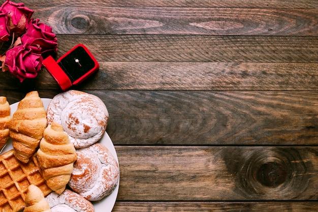 Flores, panadería en plato y anillo en caja de regalo.