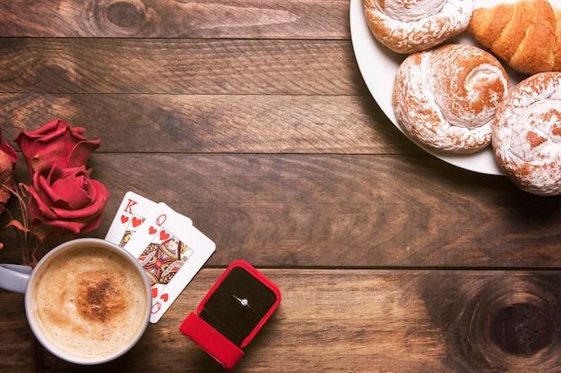 Flores, panadería en platos, anillo en caja de regalo, naipes y taza de bebida.