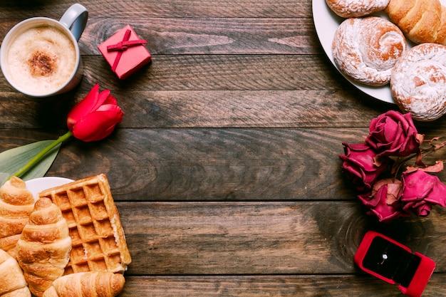 Flores, panadería en platos, anillo en caja de regalo y taza de bebida.