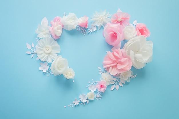Flores de papel blanco y rosa sobre rosa