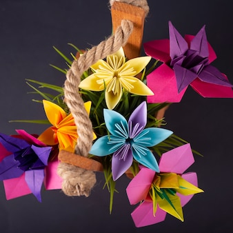 Flores de papel de colores hechos a mano origami bouquet paper craft art en una canasta con hierba en el estudio en blackbackground