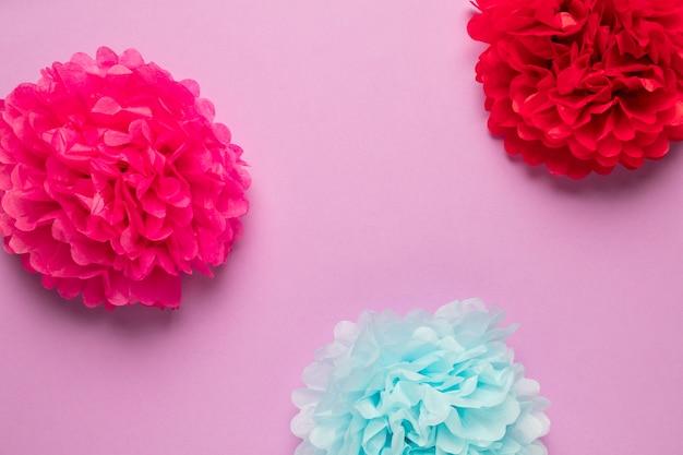 Flores de papel de colores sobre fondo rosa
