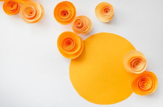 Flores de papel hechas a mano coloridas en el fondo de color claro para la invitación y la boda