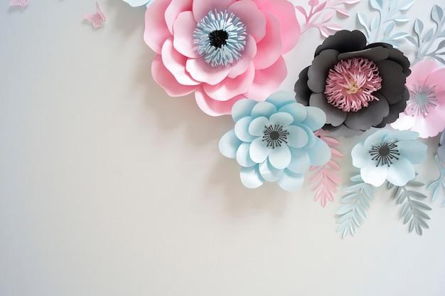 Flores de papel multicolor en colores pastel y fondo blanco.