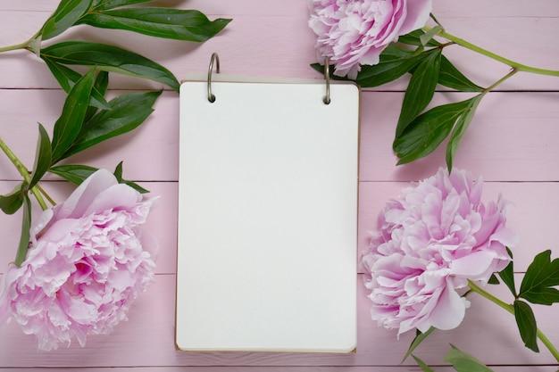 Flores de peonía con cuaderno en blanco