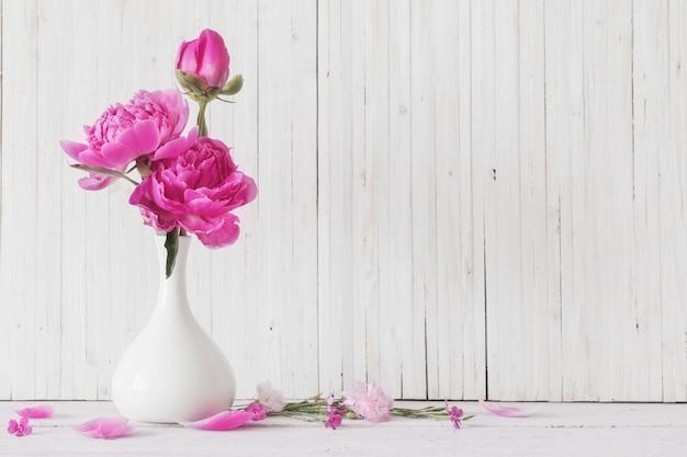 Flores de peonía en florero sobre fondo blanco.