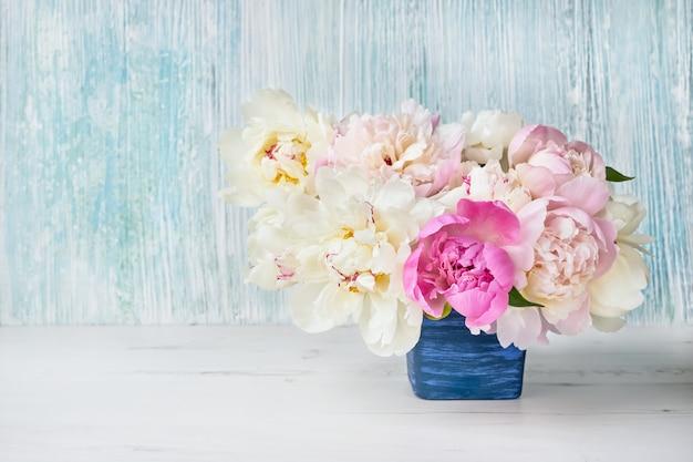 Flores de peonía en maceta azul.