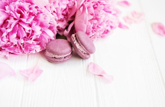 Flores de peonía rosa con macarons.