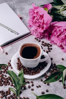 Flores peonías rosa y taza de café