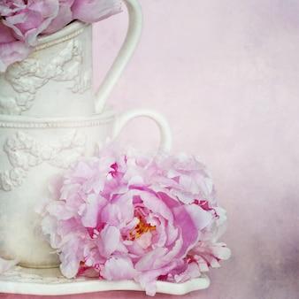 Flores de peonías y tazas de té blanco