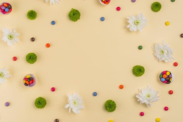 Flores con pequeños caramelos en mesa.