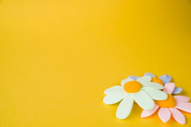 Flores planas de color pastel sobre fondo amarillo