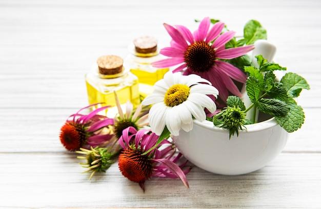 Flores y plantas medicinales en mortero y aceites esenciales sobre una mesa de madera blanca