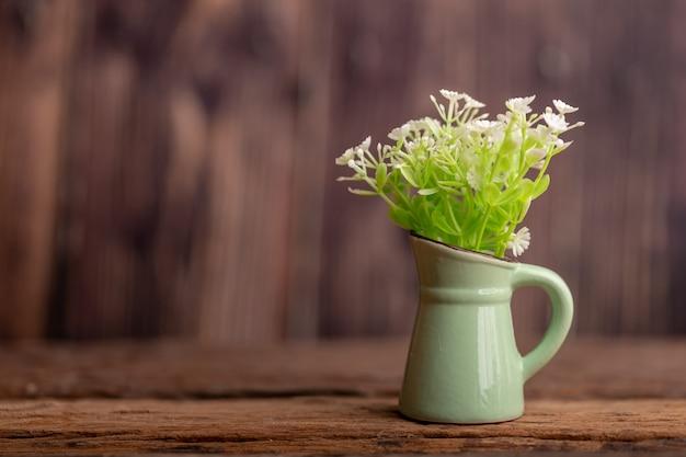 Flores de plástico en una jarra verde lugar de baldosas de cerámica en la vieja mesa de madera