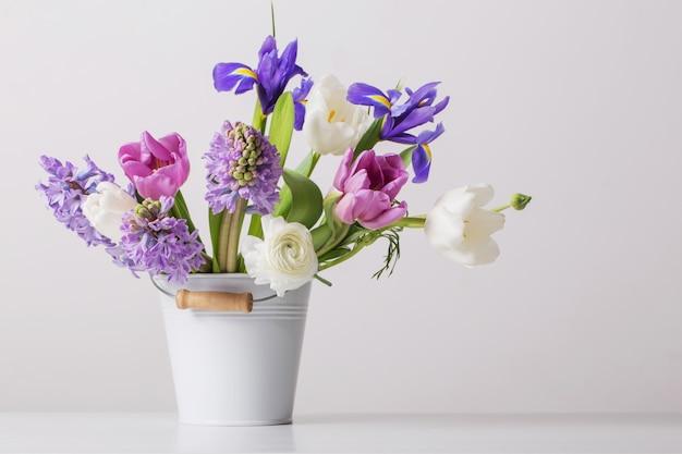 Flores de primavera en balde sobre fondo blanco.