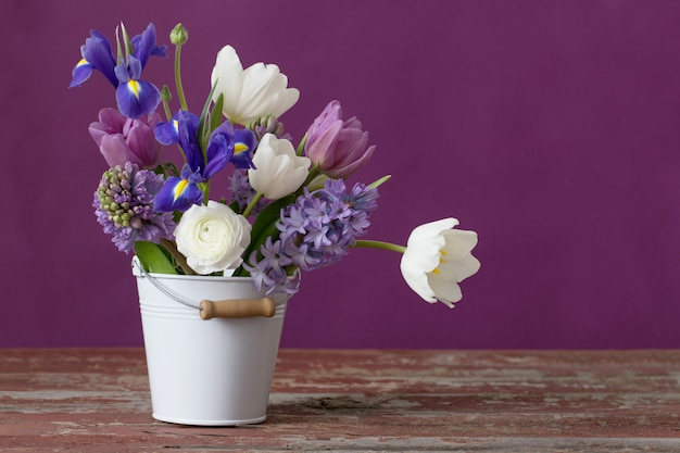 Flores de primavera en balde sobre fondo rosa