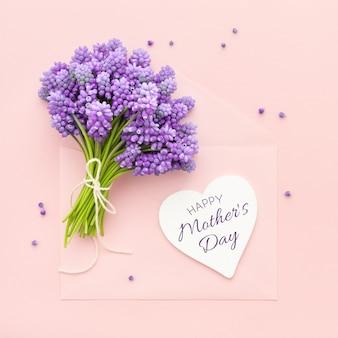 Flores de primavera de color lila y una tarjeta en forma de corazón feliz día de la madre en rosa.