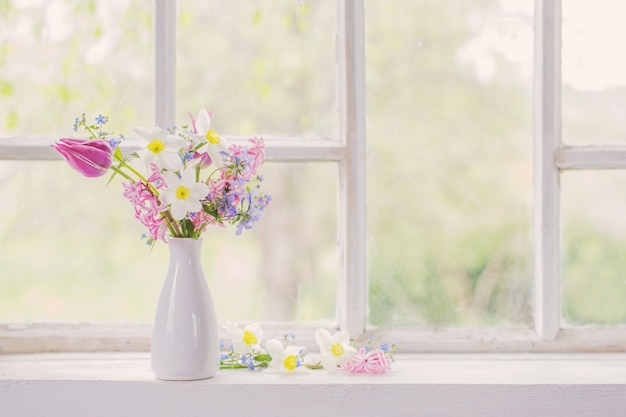 Flores de primavera en florero blanco sobre alféizar antiguo