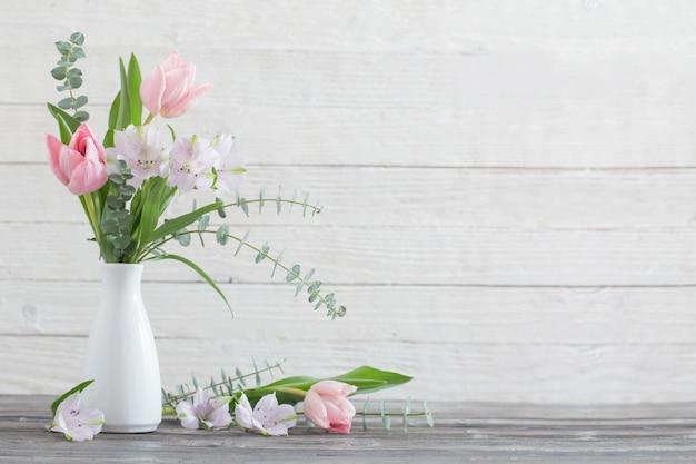 Flores de primavera en florero blanco