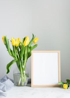 Flores de primavera en florero con marco al lado