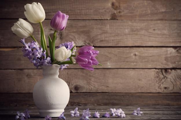 Flores de primavera en florero sobre fondo de madera vieja