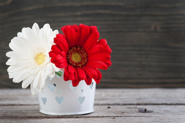 Flores de primavera en florero sobre mesa de madera.