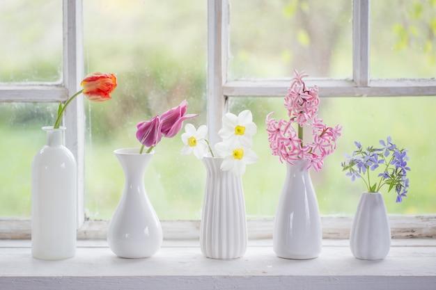 Flores de primavera en jarrón blanco en ventana vieja