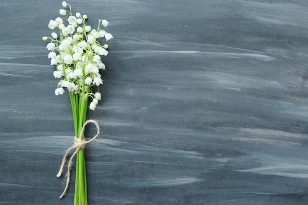 Flores de primavera lirio de los valles sobre fondo pintado vintage gris