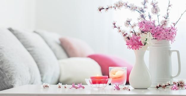 Flores de primavera rosa en florero en interior blanco