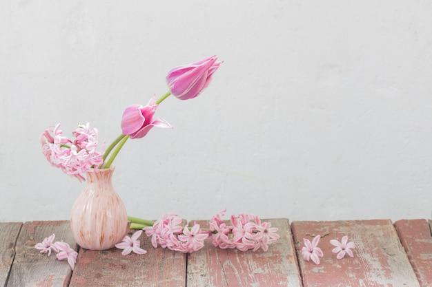 Flores de primavera rosa en mesa de madera vieja