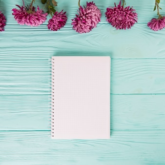 Flores púrpuras con el cuaderno en blanco en la tabla azul