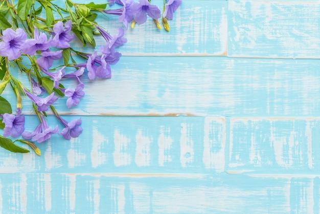Flores púrpuras en un fondo de madera azul brillante en colores pastel.