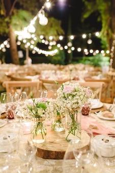 Flores que decoran los centros de mesa con cubiertos de lujo en las mesas de un salón de bodas.