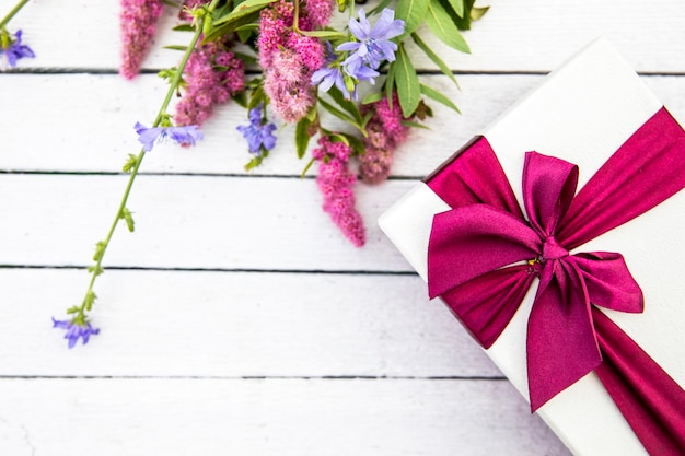 Flores y regalo sobre fondo de madera.