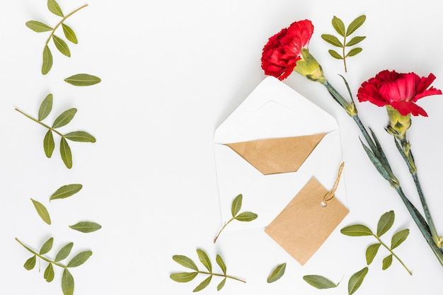 Flores rojas de clavel con sobre y papel.