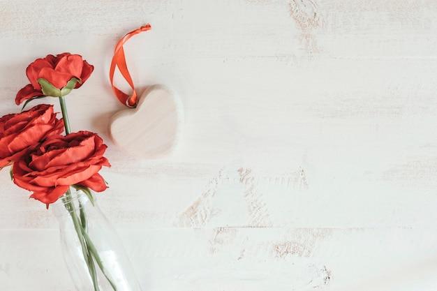 Flores rojas con corazón de madera