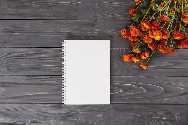 Flores rojas con cuaderno en blanco en mesa de madera