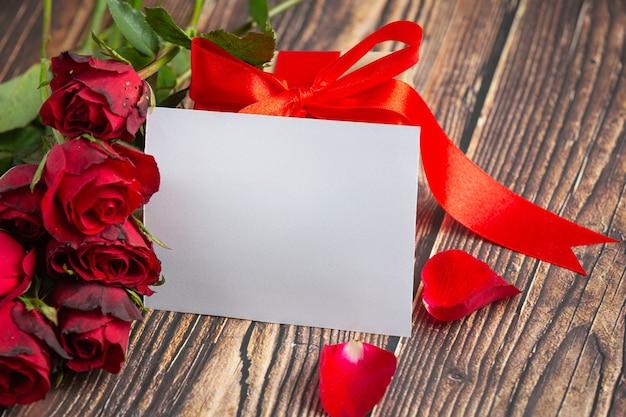 Flores rojas de rosa y envuelven sobre fondo de madera oscura.