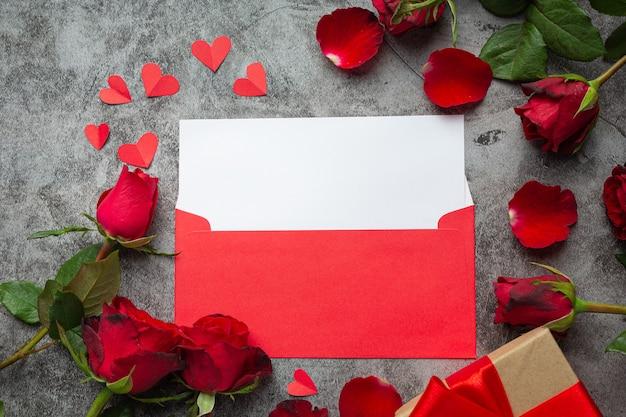 Flores rojas de rosa y envuelven sobre fondo oscuro