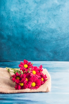 Flores rojas sobre lienzo sobre mesa.