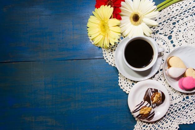 Flores románticas con café y dulces en la mesa.