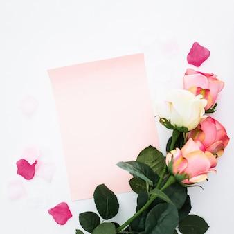 Flores románticas con papel en blanco