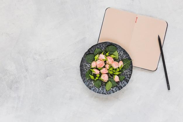 Flores rosadas en bandeja circular con diario y lápiz sobre fondo concreto